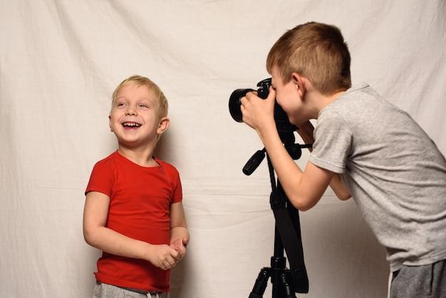 Os meninos estão se fotografando com uma câmera slr. estúdio em casa. jovem blogueiro. branco Foto Premium