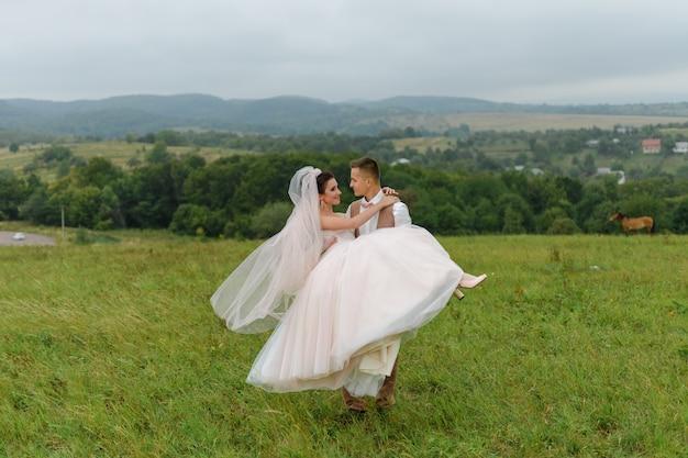 Os noivos em uma caminhada de casamento. casal apaixonado olha nos olhos um do outro. o noivo alegremente carrega a noiva nos braços. Foto Premium