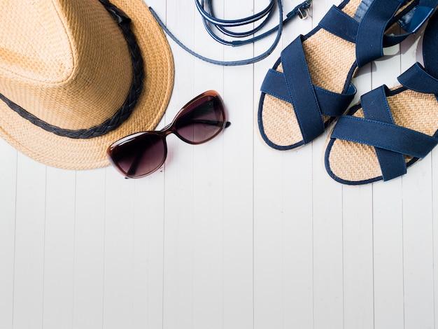 Os óculos de sol das sandálias dos braceletes do chapéu de palha do fundo do verão em uma tabela branca copiam o espaço. Foto Premium
