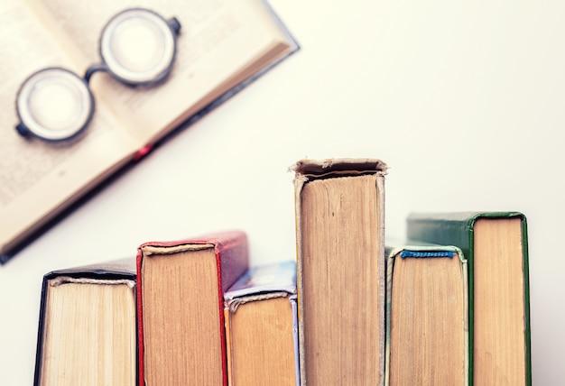 Os óculos redondos pretos estavam em cima de uma pilha de velhos livros amassados. Foto Premium