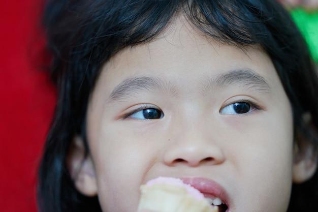 Os olhos da moça fecharam enquanto ela come e olha algo Foto Premium