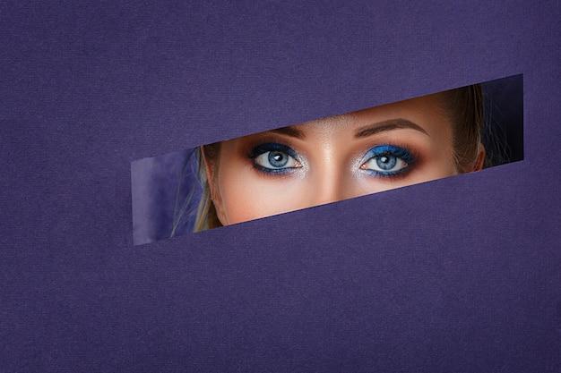 Os olhos das mulheres bonitas olham no furo de papel, composição brilhante. Foto Premium