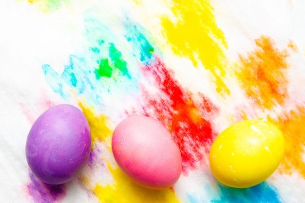 Os ovos da páscoa coloridos moldam a beira no fundo pintado multicolorido. vista de cima, copyspace Foto Premium