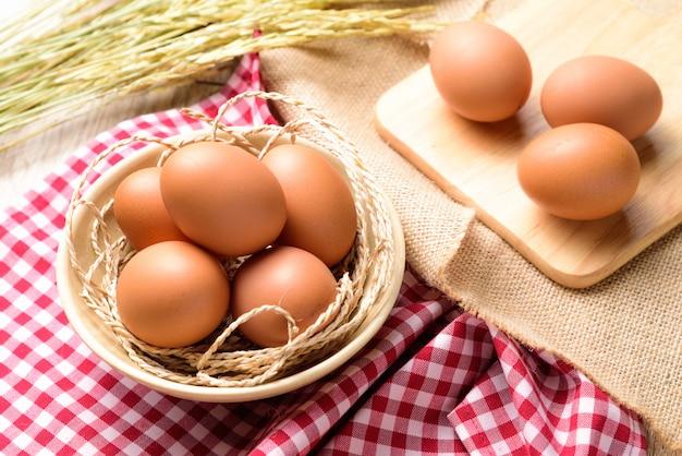 Os ovos são colocados em uma tigela branca e colocados em um xadrez escocês vermelho com orelha de arroz Foto Premium