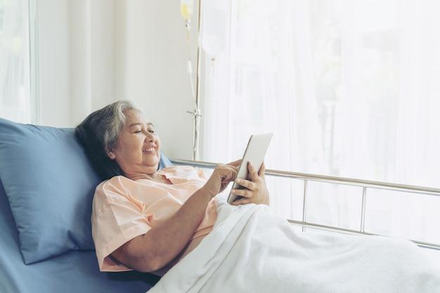 Os pacientes idosos da mulher sênior em pacientes da cama de hospital que usam o telefonema esperto aos parentes descendentes sentem a felicidade - conceito fêmea sênior da medicina e saúde Foto gratuita