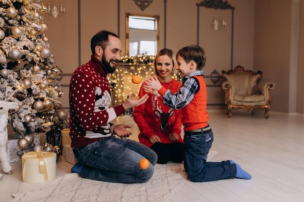 Os pais e seu filho pequeno na camisola vermelha se divertir com laranjas sentado diante de uma árvore de natal Foto gratuita