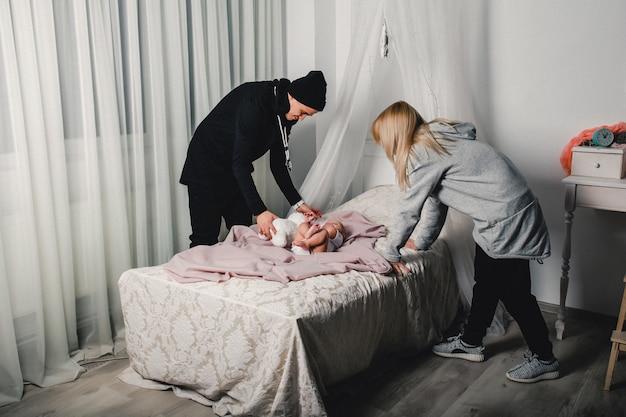 Os pais mudam o bebezinho na cama Foto Premium