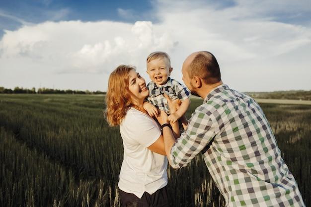 Os pais seguram o filho pequeno e se divertem Foto gratuita