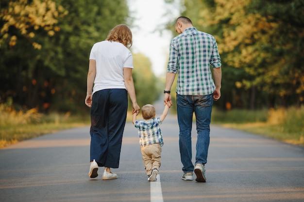Os pais segurando seu filho pequeno estão andando por uma estrada Foto gratuita