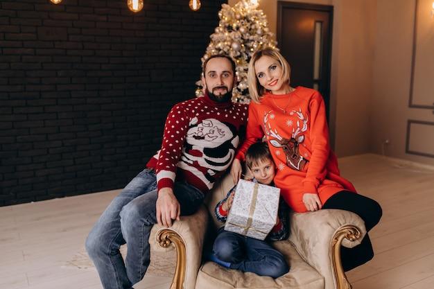 Os pais sentam-se em torno de um menino na cadeira macia antes de uma árvore de natal Foto gratuita