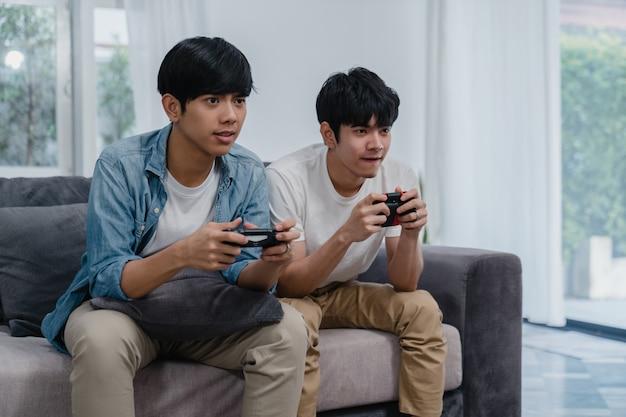 Os pares alegres asiáticos novos jogam jogos em casa, homens lgbtq coreanos adolescentes que usam o manche que tem o momento feliz engraçado junto no sofá na sala de visitas em casa. Foto gratuita