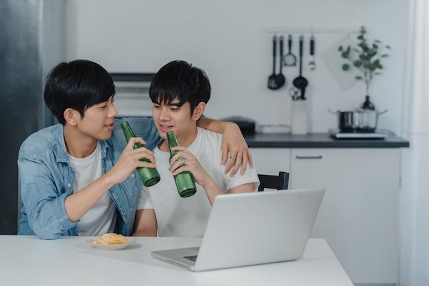 Os pares alegres novos bebem a cerveja ao usar o portátil do computador na casa moderna. os homens asiáticos lgbtq felizes relaxam o divertimento usando a tecnologia jogam mídias sociais juntos enquanto sentam a mesa na cozinha em casa. Foto gratuita