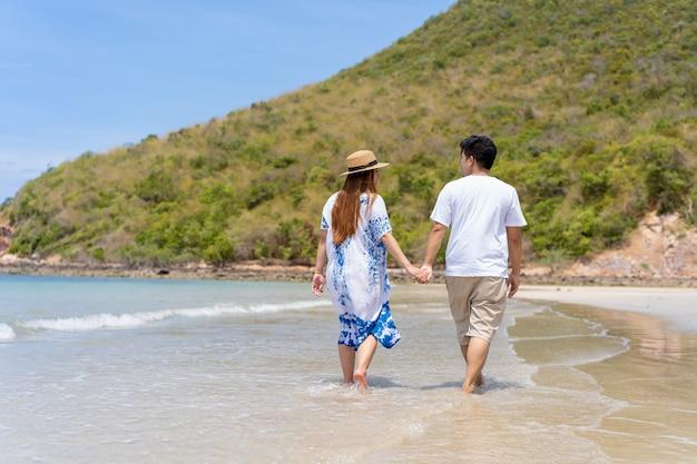 Os pares asiáticos apreciam caminhar junto a praia, conceito de família feliz e felicidade, mulher gravida que anda com seu hasband ao longo da praia. Foto Premium