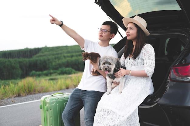Os pares asiáticos felizes e novos que apreciam a vida viajam com animais de estimação. Foto Premium