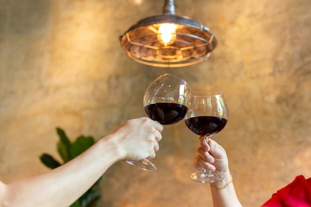 Os pares comemoram a brindar vidros do vinho tinto no restaurante. Foto Premium