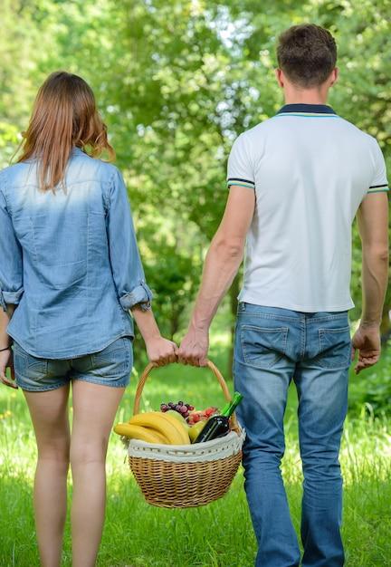 Os pares estão andando no piquenique no parque, guardando uma cesta. Foto Premium