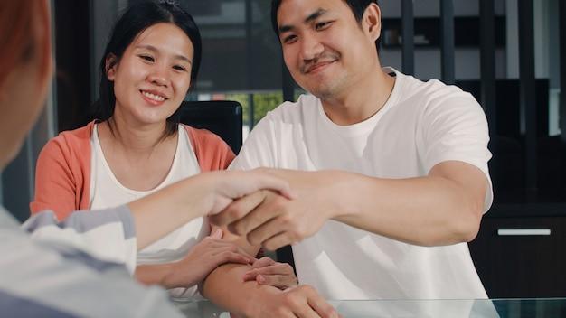 Os pares grávidos asiáticos novos assinam originais do contrato em casa, família japonesa que consulta com o conselheiro financeiro dos bens imobiliários, comprando a casa nova e o aperto de mão com o corretor na sala de visitas na manhã. Foto gratuita