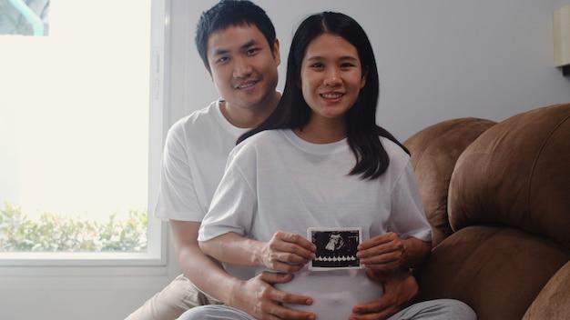 Os pares grávidos asiáticos novos mostram e olhando o bebê da foto do ultrassom na barriga. mamãe e papai se sentindo feliz sorrindo pacífica enquanto cuida criança deitado no sofá na sala de estar em casa. Foto gratuita