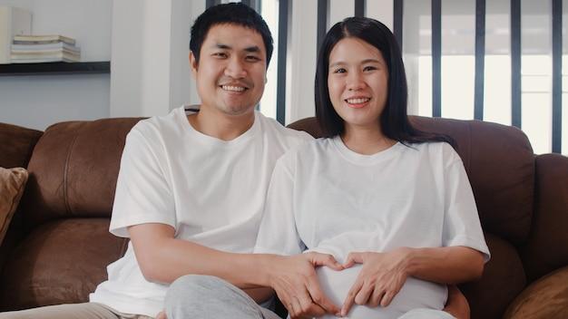Os pares grávidos asiáticos novos que fazem o coração assinam guardar a barriga. mamãe e papai se sentindo feliz sorrindo pacífico enquanto cuidar bebê, gravidez, deitado no sofá na sala de estar em casa. Foto gratuita