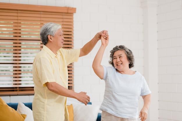 Os pares idosos asiáticos que dançam junto quando escutam a música na sala de visitas em casa, par doce apreciam o momento do amor ao ter o divertimento quando relaxado em casa. Foto gratuita