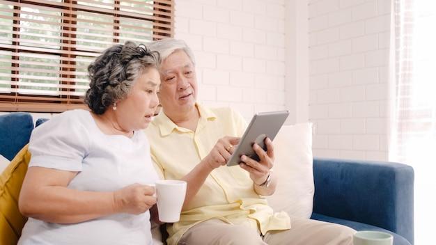 Os pares idosos asiáticos que usam a tabuleta e bebendo o café na sala de visitas em casa, pares apreciam o momento do amor ao encontrar-se no sofá quando relaxado em casa. Foto gratuita