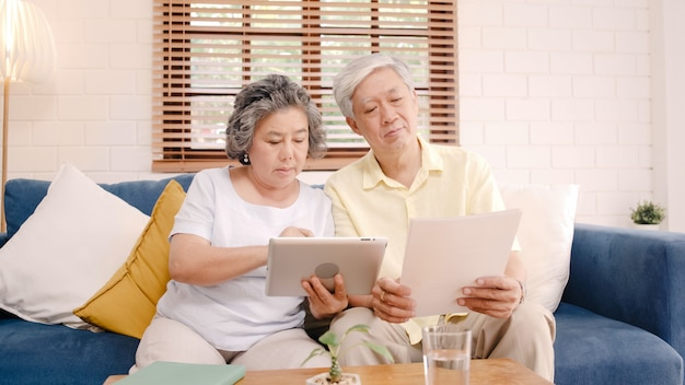 Os pares idosos asiáticos que usam a tabuleta que olha a tevê na sala de visitas em casa, pares apreciam o momento do amor ao encontrar-se no sofá quando relaxado em casa. Foto gratuita