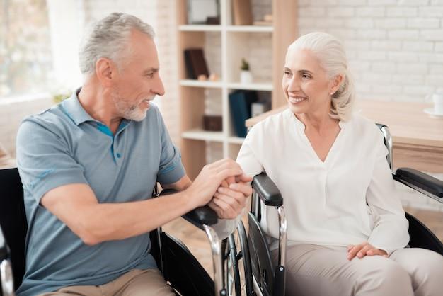 Os pares idosos felizes na cadeira de rodas prendem as mãos. Foto Premium