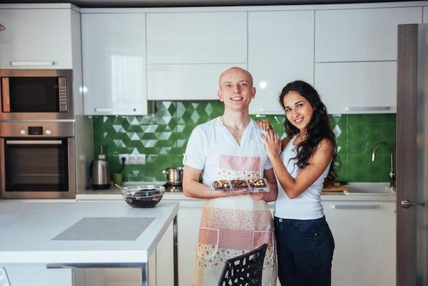 Os pares novos bonitos representaram graficamente miling na câmera ao cozinhar na cozinha em casa. Foto Premium