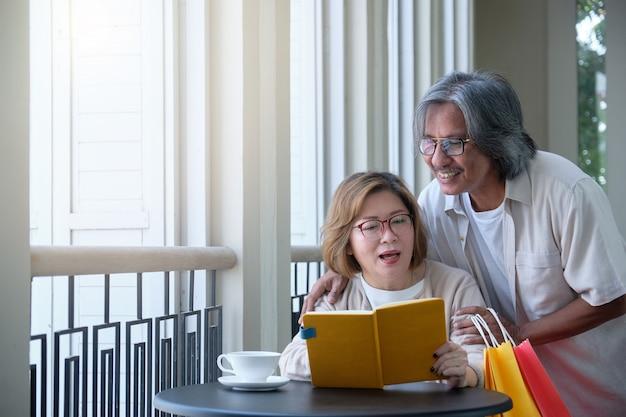 Os pares superiores vão às compras, leem livros e bebem o café em férias, conceito de família feliz. Foto Premium