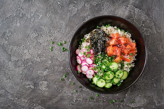 Os peixes havaianos puxam a bacia com o arroz, o rabanete, o pepino, o tomate, as sementes de sésamo e as algas. Foto Premium