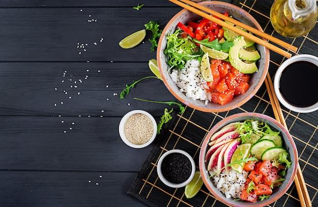 Os peixes salmon havaianos puxam a bacia com arroz, abacate, paprika, pepino, rabanete, sementes de sésamo e cal. Foto Premium