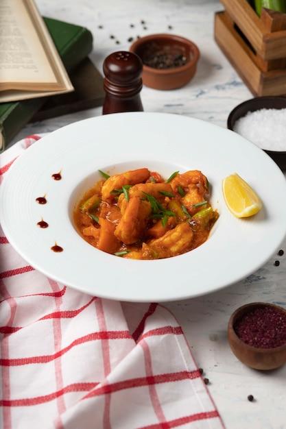 Os pés da galinha stew no molho de tomate na bacia branca com vegetais e limão. Foto gratuita