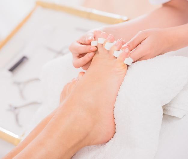 Os pés da mulher em separadores do dedo do pé do pedicure no salão de beleza do prego. Foto Premium