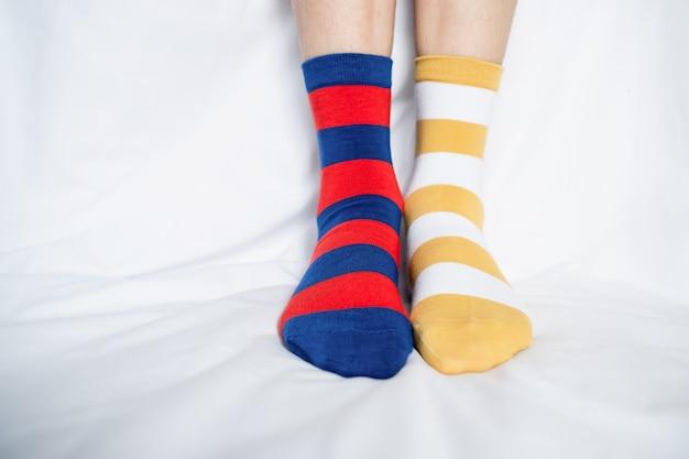 Os pés das mulheres nas peúgas colorem a alternação, suporte lateral no assoalho branco da tela. Foto Premium