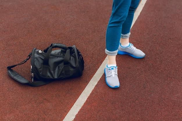Os pés de tênis cinza estão parados perto da linha branca no estádio. há uma sacola esportiva preta próxima. Foto gratuita