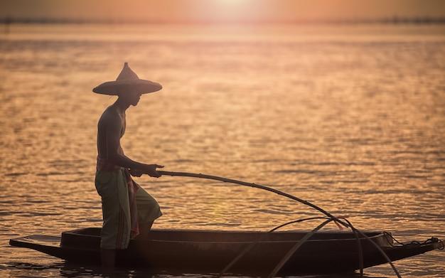 Os pescadores estão usando ferramentas de pesca pela manhã ao longo do lago songkhla Foto Premium