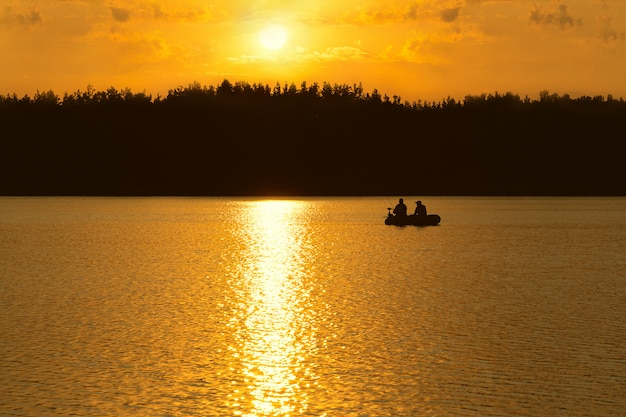 Os pescadores pegam peixes no lago ao pôr do sol. Foto Premium