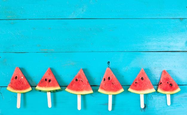 Os picolés de fatia de melancia verão em um fundo azul de madeira rústica. Foto Premium