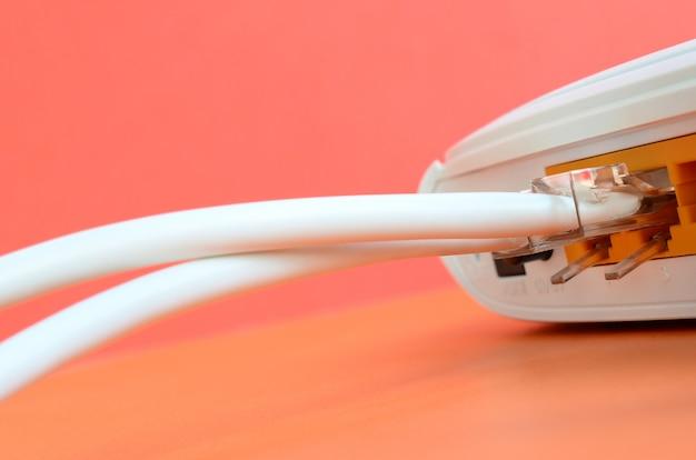 Os plugues do cabo de internet estão conectados ao roteador de internet, que fica em um fundo laranja brilhante Foto Premium