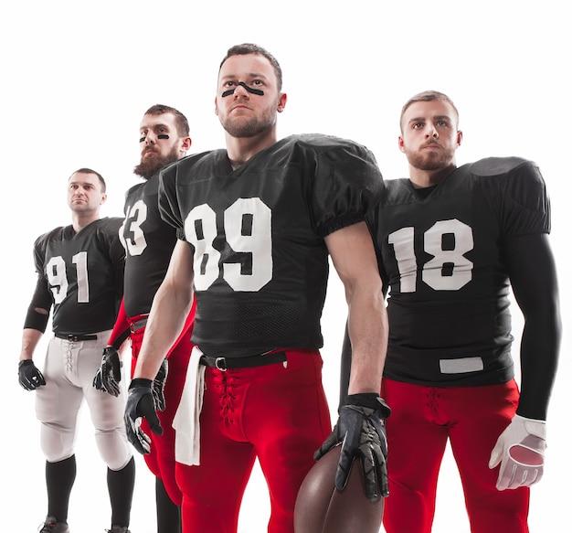 Os quatro homens caucasianos de fitness como jogadores de futebol americano posando de corpo inteiro com uma bola no fundo branco Foto gratuita