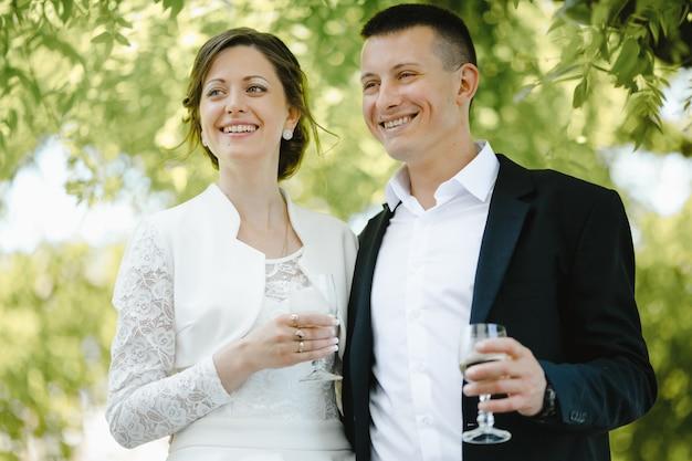 Os recém-casados sorriem e mantêm copos com champanhe Foto gratuita