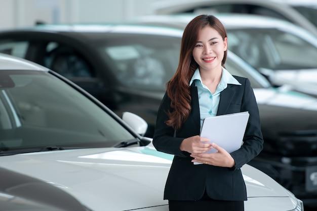 Os revendedores de automóveis asiáticos bonitos estão felizes em vender carros novos no showroom e gostam de vender carros. Foto Premium