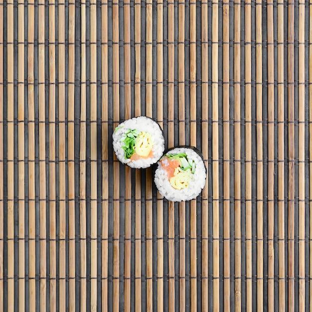 Os rolos de sushi encontram-se em uma esteira de serwing de bambu da palha. comida asiática tradicional. Foto Premium
