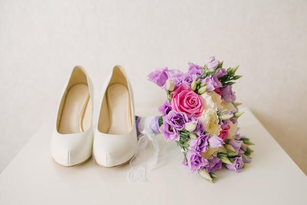 Os sapatos da noiva e buquê de noiva lilás rosa fica ao lado do fundo branco, os acessórios da noiva Foto Premium