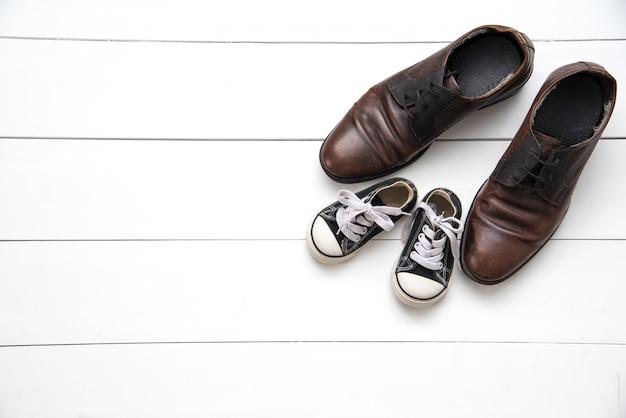 Os sapatos de pai e filho no fundo branco madeira - conceito cuidar Foto Premium