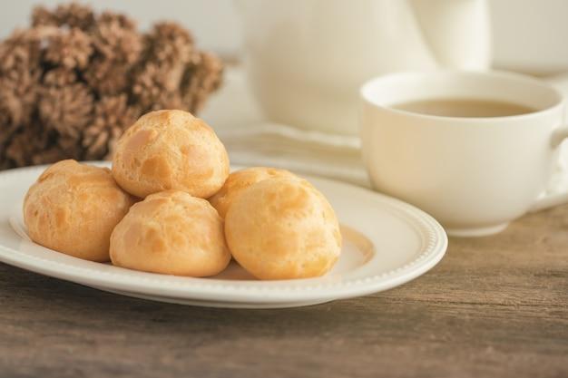Os sopros de creme caseiros ou o creme do eclair ou dos choux serviram com chá na tabela de madeira. Foto Premium