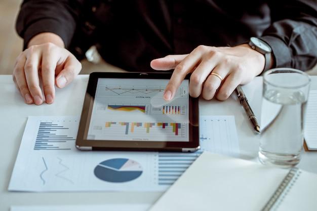 Os tablet pc do uso do homem de negócios para conectar com a palavra para analisam o comércio da economia. ele é casado. Foto Premium