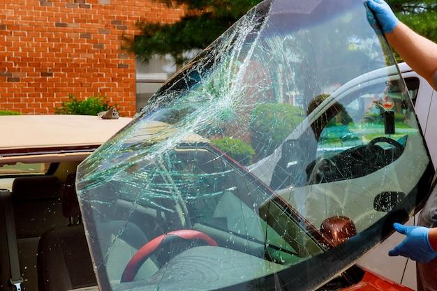 Os trabalhadores especiais do carro do para-brisa quebrado tomam do para-brisa de um carro no auto serviço Foto Premium