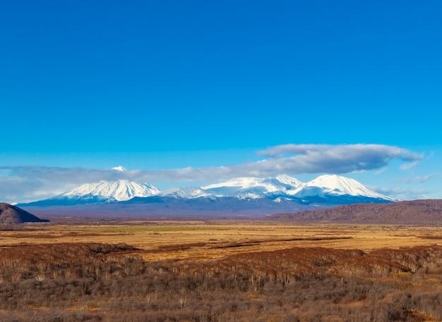 Os três vulcões de neve na península de kamchatka Foto Premium