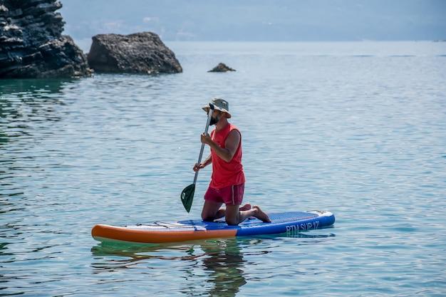 Os turistas estão empenhados em remar no tabuleiro (sup) na superfície do mar calmo. Foto Premium